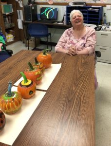A woman served in CLI's ROW program smiles in front of a long line of decorated pumpkins.
