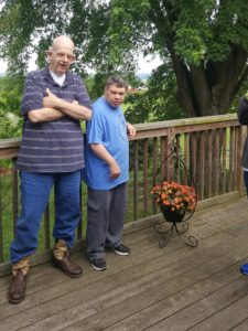Two residents of a CLI house stand on their porch.